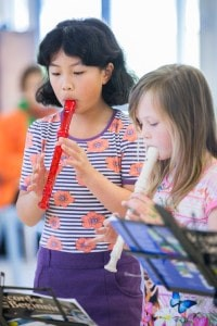 Two girls playing the recorder